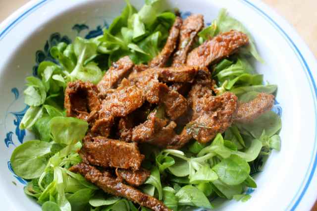 spicy beef on green salad